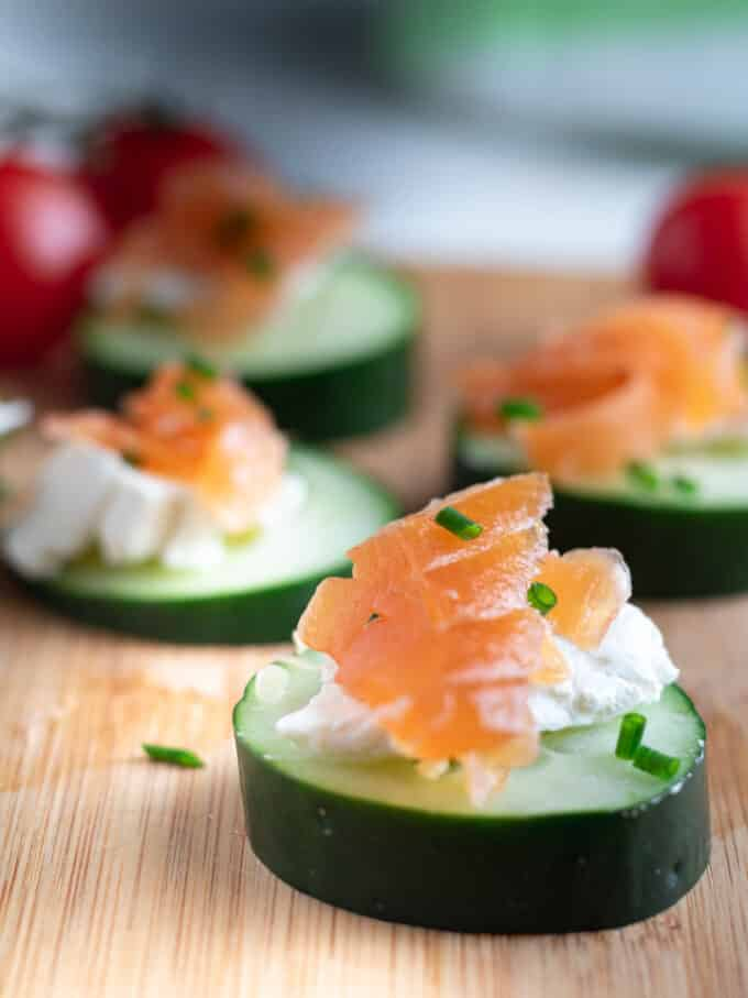 Close up slice of cucumber topped with cream cheese and lox.