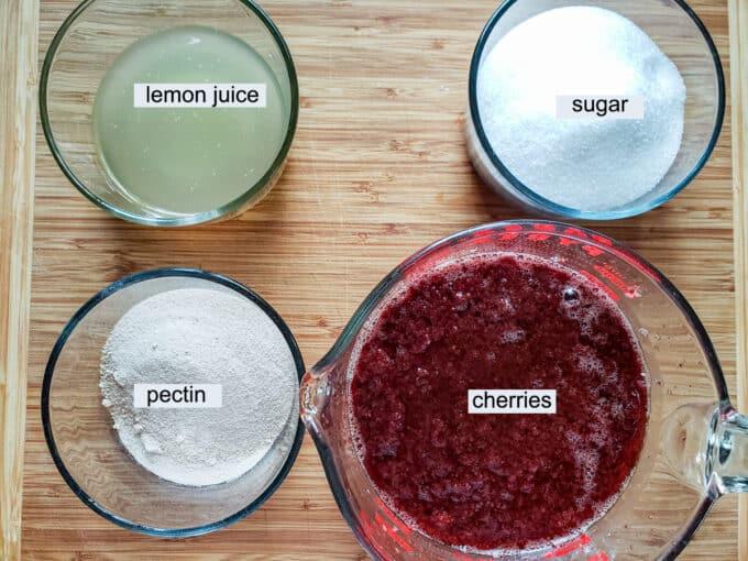 Ingredients for cherry jam- lemon juice, sugar, pectin, cherries with juice.