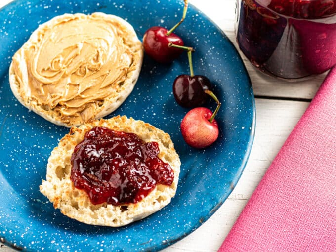 English muffin with cherry jam on half and peanut butter on half.