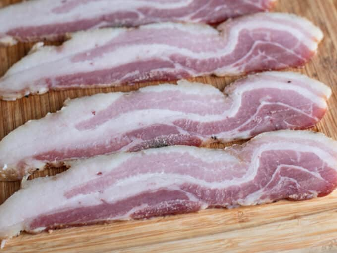 Slices of uncooked bacon on cutting board.