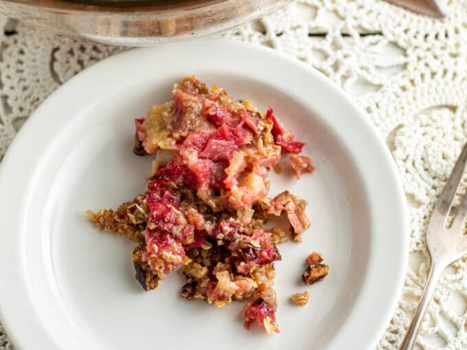 Serving of colorful rhubarb crisp on white plate.