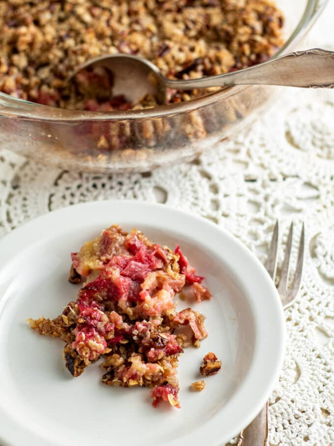 Plate of rhubarb crisp with baking dish in background.