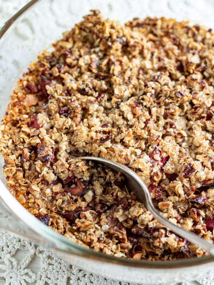 Whole rhubarb crisp dessert with silver spoon.