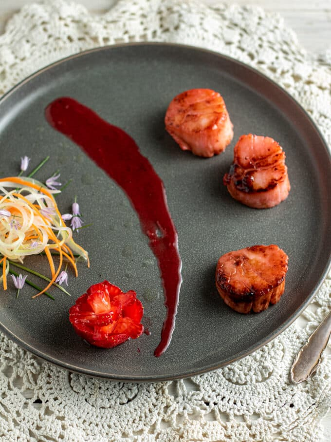 Overhead photo of scallop dinner with strawberry sauce on gray plate.
