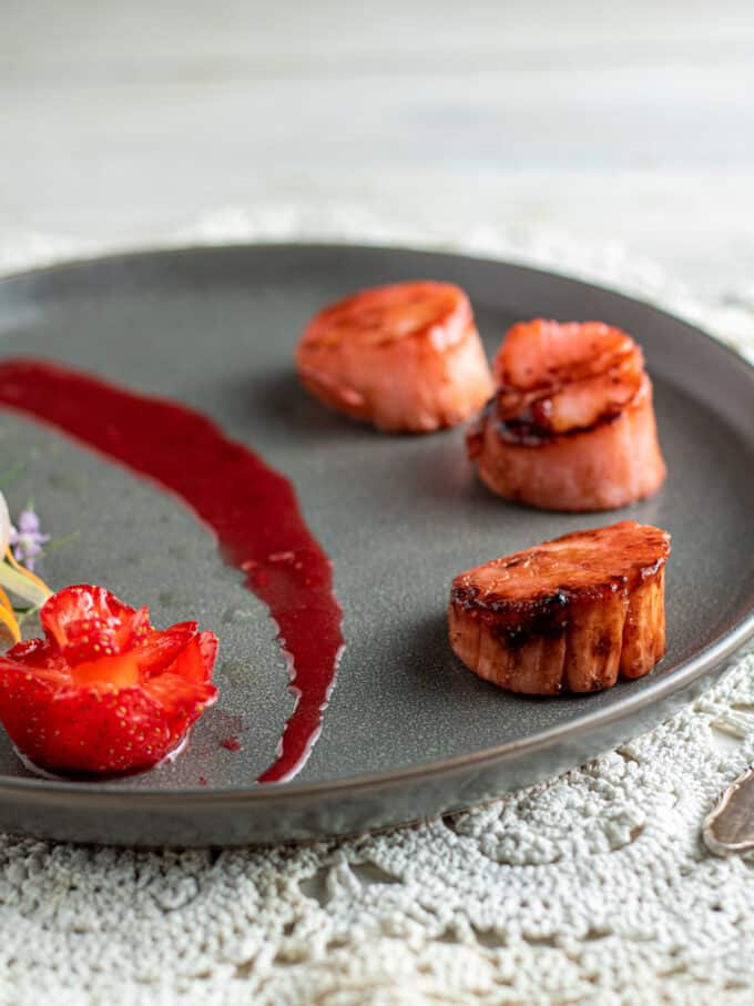 3 strawberry scallops on gray plate.