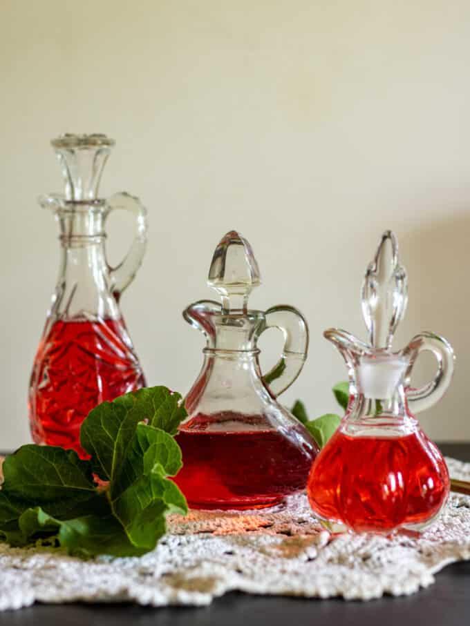 Red rhubarb vinegar in 3 different cruets.