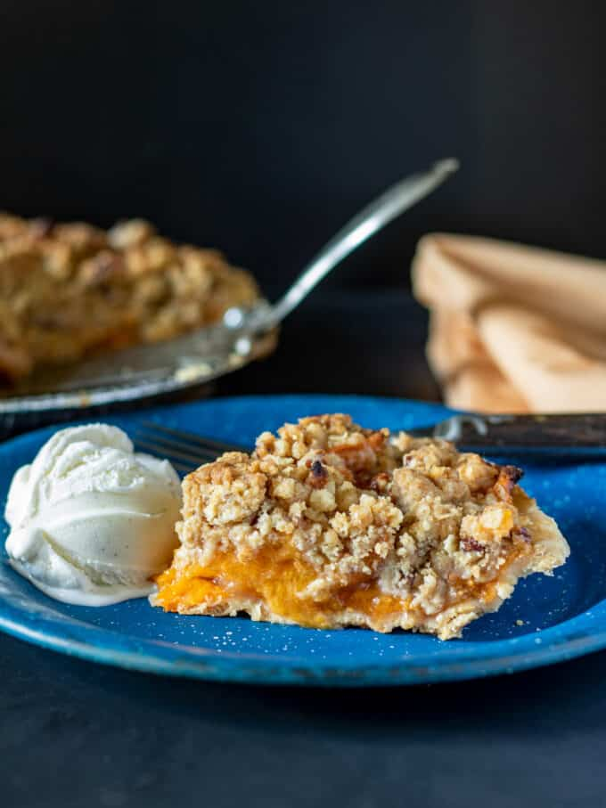 Slice of apricot pie on blue enameled plate.