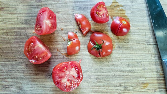 Halved tomatoes on cutting board.