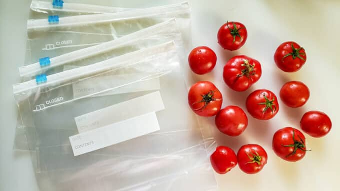 Fresh tomatoes and freezer bags on white board.