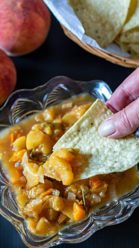 Hand holding tortilla chip dipping into peach salsa.