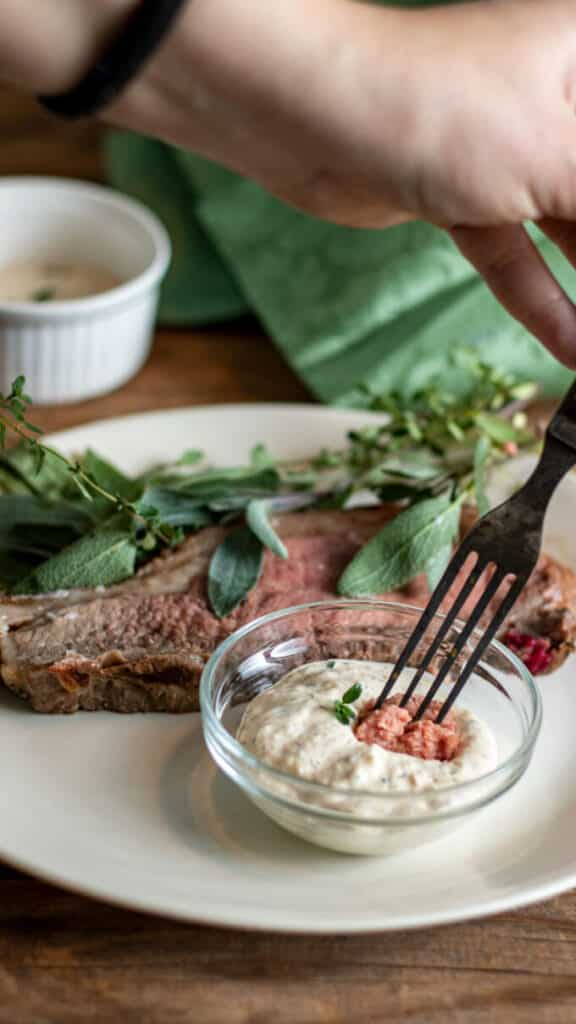 Fork dipping piece of beef into horseradish sauce.