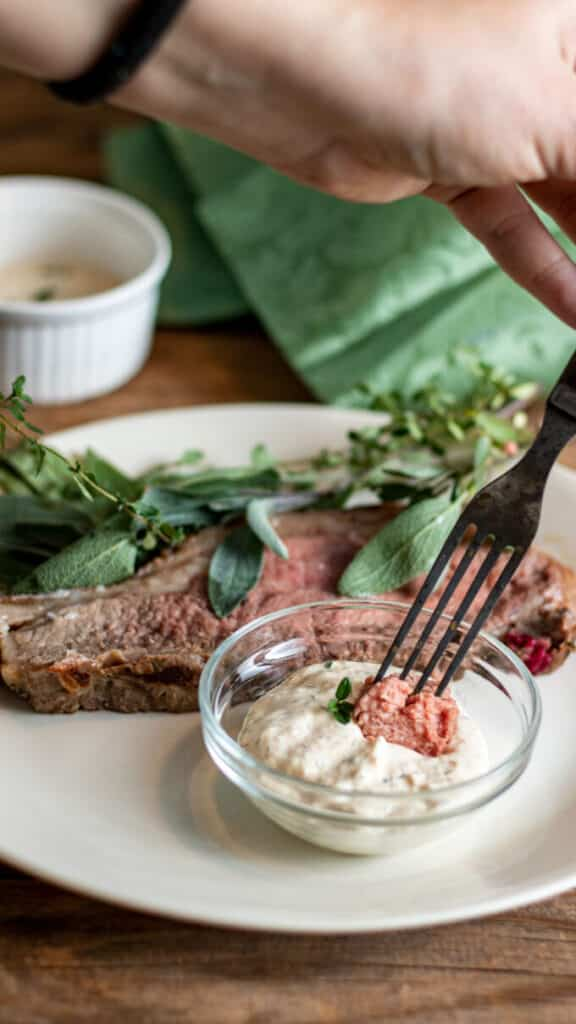 Hand holding fork and dipping cut steak into horseradish sauce.