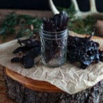 Woodland scene with venison jerky in a canning jar.