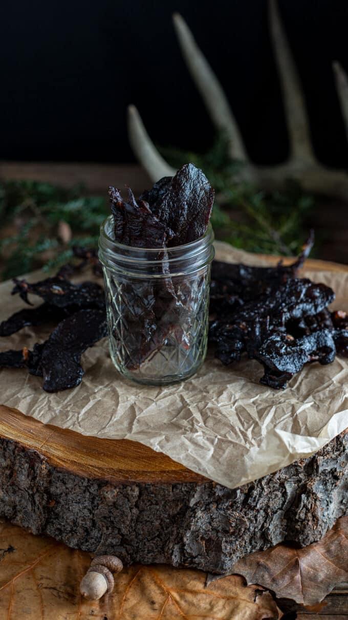 Jerky in jar in woodland scene.