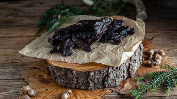 Pile of jerky on tree slab.