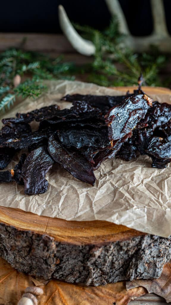 Close up of jerky on slab of wood.