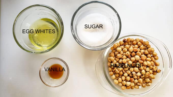 Ingredients used in cookies. Egg whites, sugar, vanilla and hazelnuts.