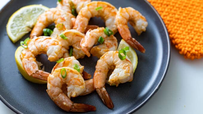 Shrimp placed on grey plate with chive garnish.