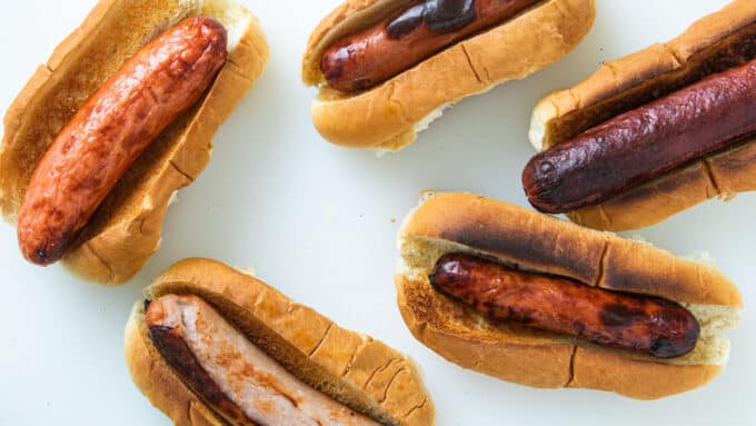 Five assorted hot dogs on rolls.
