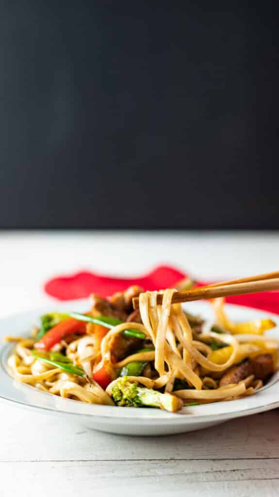 Chopsticks lifting noodles in a side view.