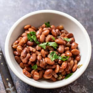 Bowl of whole beans topped with chopped cilantro.