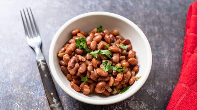 White bowl filled with beans and topped with cilantro.