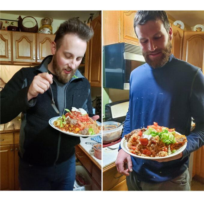 Two men eating pork enchiladas.