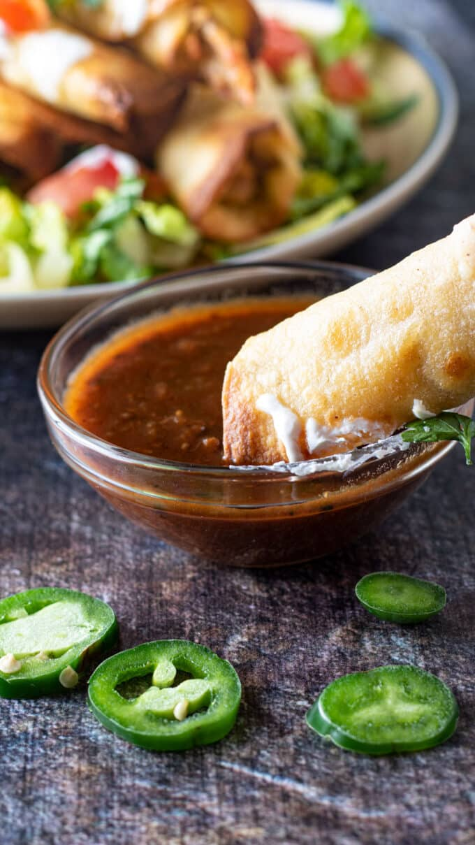 Hand dipping taquito in salsa.