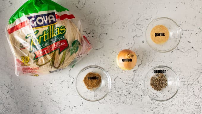 Ingredients for taquitos; tortillas, onion, spices.