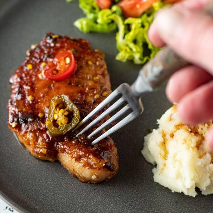 Fork stabbing pork chop.