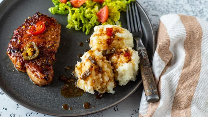 Chops, mashed potatoes and salad on plate.