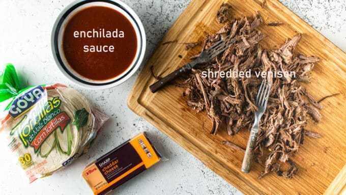 Ingredients to make enchiladas; pulled venison enchilada sauce, tortillas, cheese.