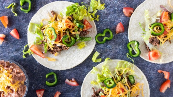 Overhead photo of 3 venison tacos with toppings.