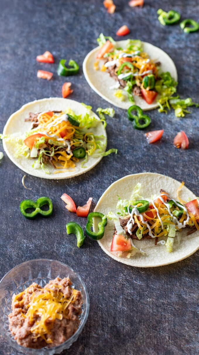 Tacos with beans and garnished with jalapeno peppers.