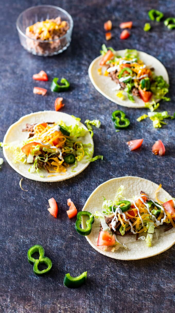 Three tacos garnished with lettuce, tomatoes, cheese and chillies.
