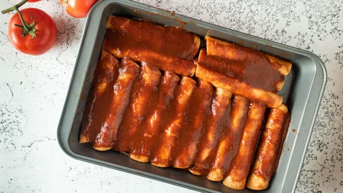 Assembled enchiladas in baking tray before baking..