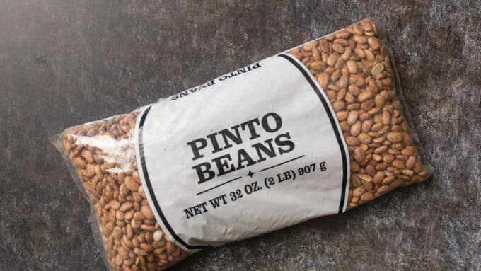 Bag of Pinto beans on gray background.