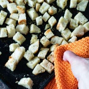 Hand holding potholder picking up hot tray.
