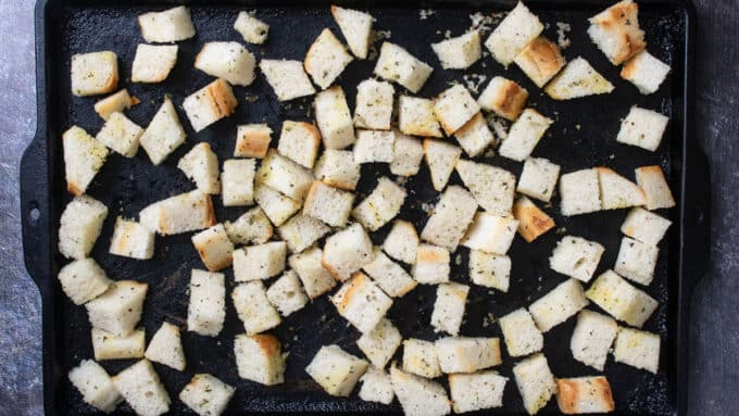 Unbaked croutons on antique baking tray.