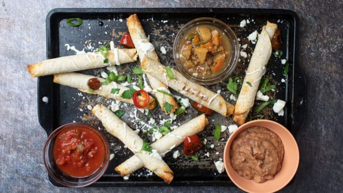 Overhead photo of taquitos with colorful toppings.