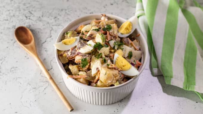 Potato salad in bowl with serving spoon.