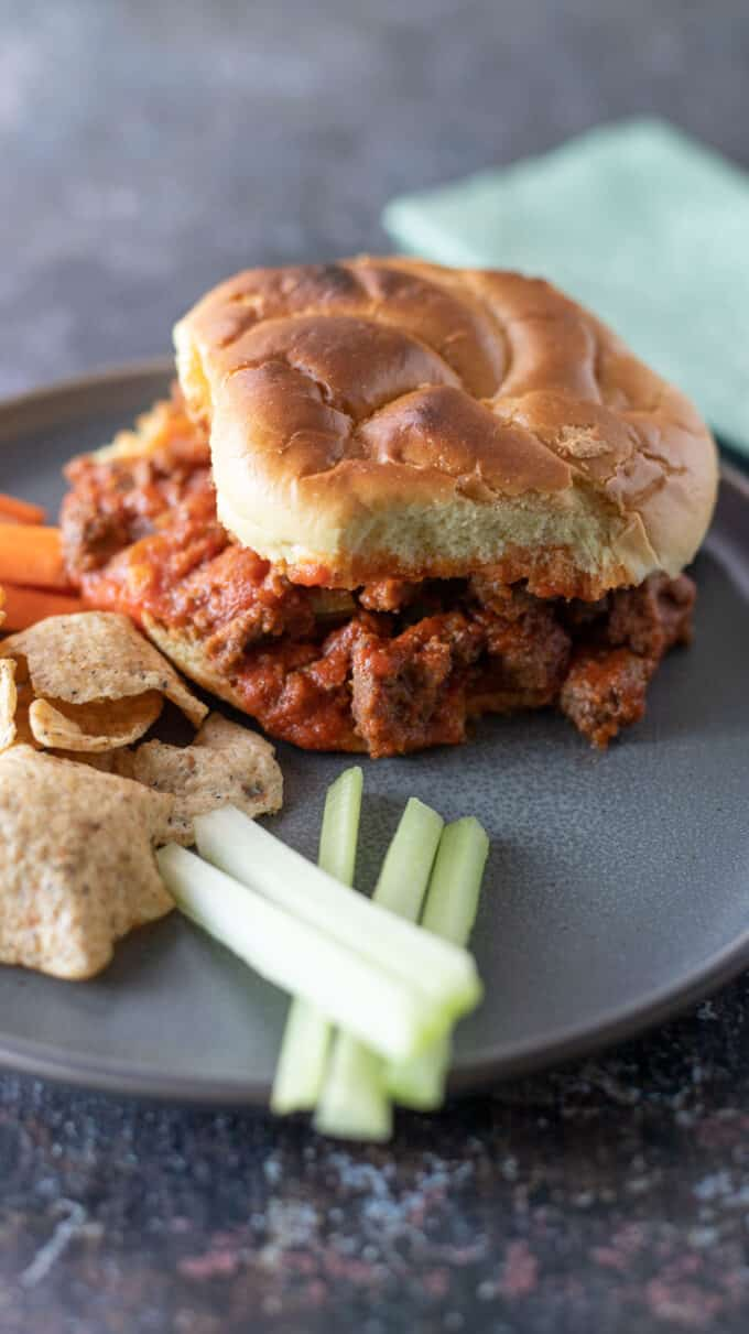 Sloppy joe on gray plate with chips and vegetables.