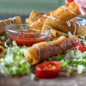 Woman's hand dunking taquitos in salsa.