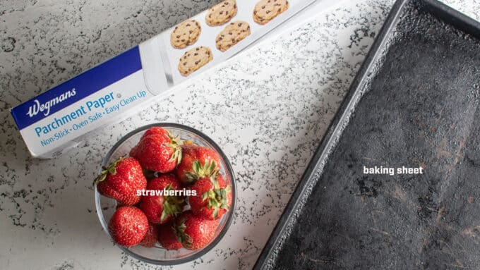 Equipment needed to freeze strawberries. Parchment, baking sheet, strawberries.