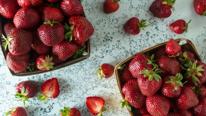 Two quarts of fresh strawberries in antique baskets.