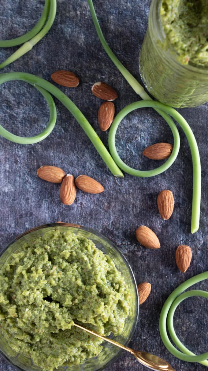Overhead photo of pesto with almonds and scapes.