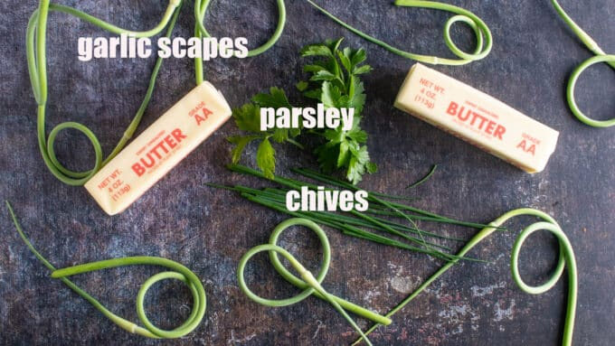 Garlic scapes, chives, parsley and butter on dark board.
