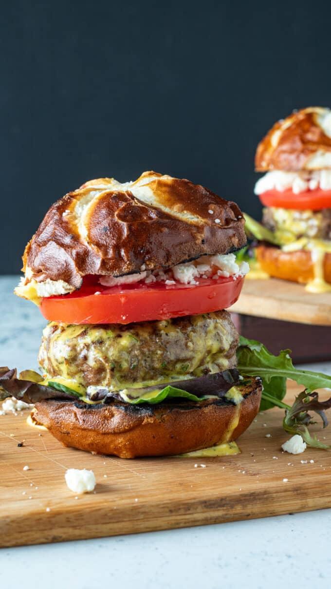 Juicy lamb burger on pretzel bun on wooden cutting board.