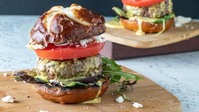 Piled high feta lamb burger with aioli and toppings.