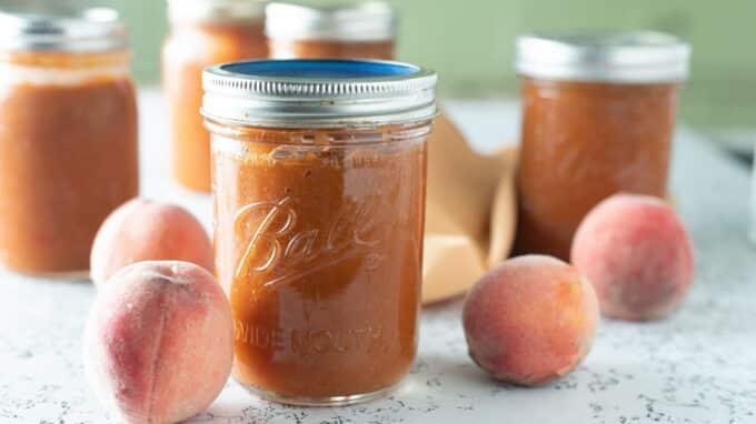 Peach bourbon BBQ sauce with fresh peaches in photo.